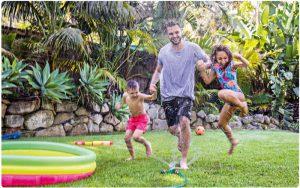 Familie läuft durch Sprinkler im Garten