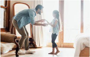 Vater tanzt mit Kind in Zimmer, Wohlfühlatmosphäre